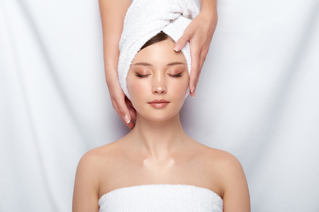 Photo pour attractive woman lying down on spa theraphy in bath towel, customer of spa receiving facial treatment with beautician - image libre de droit