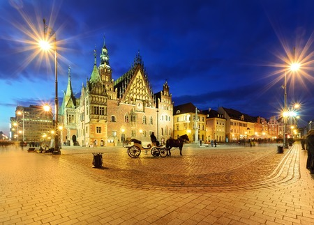 Foto de Horse carriages at main square in Wroclaw near the town hall in the evening, Poland - Imagen libre de derechos