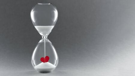 Photo pour Hourglass on dark background. Symbol of Time for love. Concept passing love. - image libre de droit