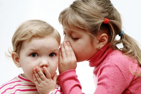 An image of a girl whispering something to a baby