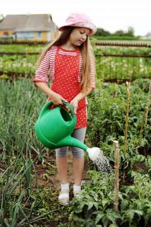 Girl watering plants in a kitchen-garden