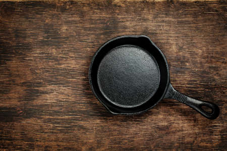 Vintage cast iron skillet on rustic wood background.