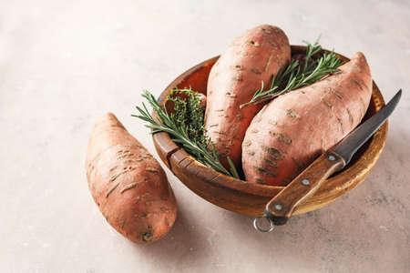 Photo pour Organic sweet potatoes in a wooden bowl - image libre de droit