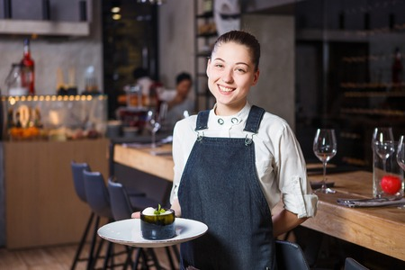 Photo pour young girl with a beautiful smile a waiter holds in her hands an order sweet dessert dish of Italian cuisine. Dressed in a crusty apron and a white shirt behind the interior of the restaurant - image libre de droit
