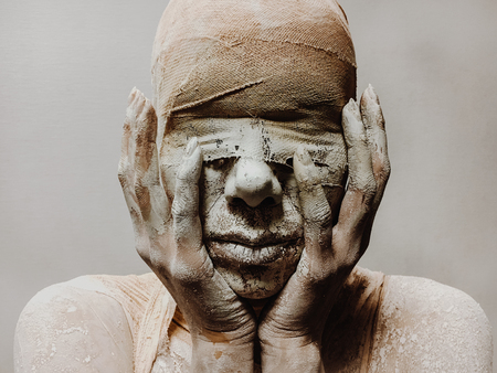 in makeup, a woman in bandages and clay is like a mummy without eyes on a monophonic background. Halloween theme