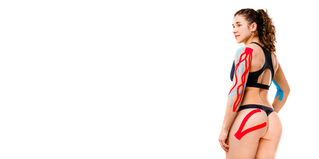 sexy female athlete with beautiful booty stands half sideways on white background in black top and bikini.On body is pasted kinesiology tape.Colored tapes for treatment of muscles,tendons in athletes.
