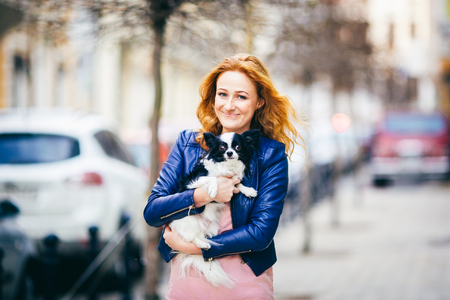 Subject man and dog. A young red-haired Caucasian woman with freckles on face holds black and white shaggy chihuahua breed dog. The girl dressed in blue leather jacket, stands on busy street in spring