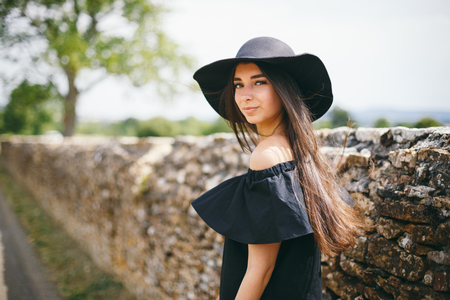 beautiful young sexy woman model of brunette with dark skin in black dress and hat with fields, fashionably dressed standing in French village a burgundy on road against rocky fence in sunny weather.
