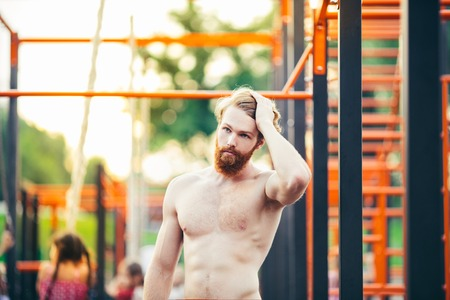 Subject sport street workout Handsome young caucasian man with a bare-chested muscular with long red hair and beard posing outdoor sports ground, gym outdoors. Sexy guy touches his hair