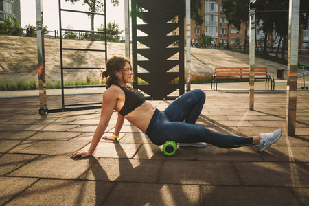 Photo pour theme sport and rehabilitation sports medicine. Beautiful strong slender Caucasian woman athlete uses foam roller green field street workout to workout to remove pain, stretch and massage muscles. - image libre de droit