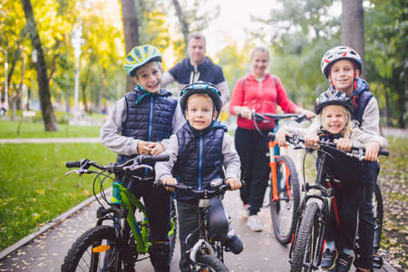 Photo pour Theme family sports vacation in park in nature. big friendly Caucasian family of six people mountain bike riding in forest. Children brothers and sister stand on the background of parents in a row. - image libre de droit