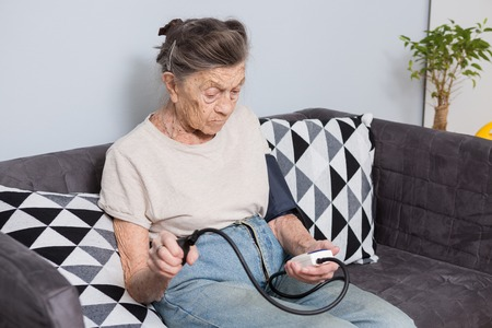 The topic is very old person and health problems. A senior Caucasian woman, 90 years old, with wrinkles and gray hair, sits home on sofa and uses a blood pressure monitor to measure blood pressure.