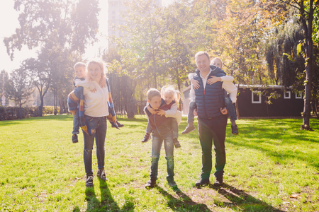 Photo for Theme family active leisure outside in nature. large Caucasian family with four children. Mom and Dad actively relaxing. enjoy life in park near house on grass. Children on back shoulders roll on top. - Royalty Free Image