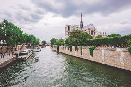 Photo pour July 23, 2017. Paris, France. Notre dame cathedral from river Seine in Paris. Notre dame cathedral from river Seine Paris, France. Beautiful view of a canal-boat and the Notre-Dame Cathedral. - image libre de droit