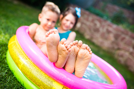 Foto de Theme summer vacation. Two children Caucasian brother and sister lie in water, inflatable home round pool in yard on green grass. Close-up of feet sole heels children in hot summer weather. - Imagen libre de derechos