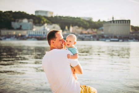 Foto de Subject recreation father and little son. Young caucasian dad sits on wooden bench overlooking the town Kiev and holding river of the Dnieper, hugging a toddler baby on sandy beach on the banks pond. - Imagen libre de derechos