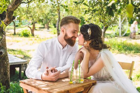 Photo for Attractive couple newlyweds, happy and joyful moment. bride and groom sit at table set for two in woods. Concept romantic date. Wedding couple sitting in cafe table and lovingly look at each other. - Royalty Free Image