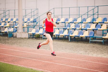 Photo for Female runner jogging on stadium track, woman athlete running and working out outdoors, sport and fitness concept. Young woman in sportswear training on a stadium. Sport lifestyle topic. - Royalty Free Image