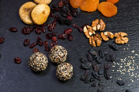 Photo pour Theme sweet dessert made from natural products without sugar. Macro close-up of deserts ball round candy truffle on a black plate with natural dried fruit and seeds of white and black sesame and flax. - image libre de droit