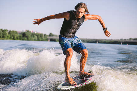 Photo for Active wakesurfer jumping on wake board down the river waves. Surfer on wave. Male athlete training on wakesurf training. Active water sports in open air on board. A man catches a wave on surf. - Royalty Free Image