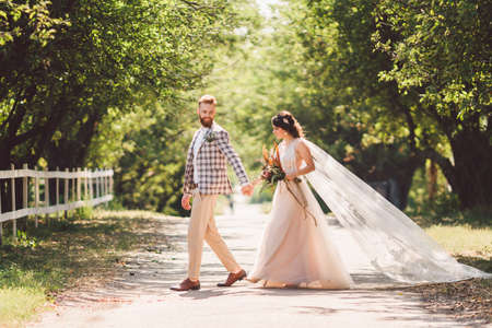 Photo pour Lovely wedding couple wood forest. Bride and groom, follow me, married couple, woman in white wedding dress and veil. Rustic outdoors love story. Follow me hipster photo. newlyweds holding hand walk. - image libre de droit