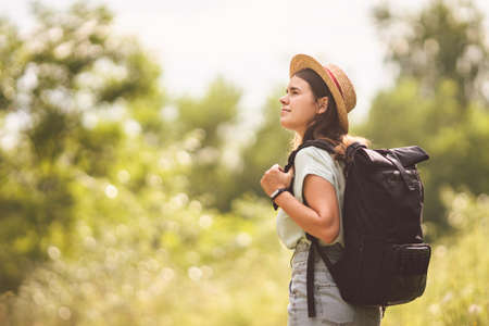 Photo for Stylish fashionable hipster traveler woman in hat with brim and roll top type backpack walking in nature. Travel and wanderlust concept. Exploring nature, hot summer day. Outdoor activity. Wanderlust. - Royalty Free Image