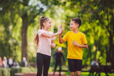 Foto de Sports and fitness in adolescence. Caucasian twins boy and girl run on the jogging track in the city park. Two children brother and sister for 10 years running on a rubberized outdoor treadmill. - Imagen libre de derechos