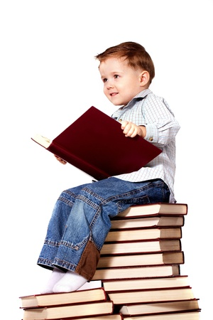 little boy sitting on a pile of books