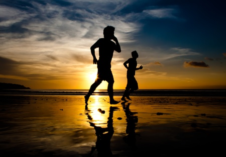 Two men running on Jimbaran beach at sunset