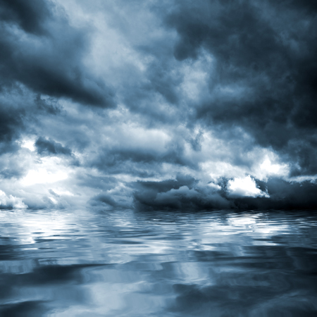 Dark storm clouds before rain above the water level. Natural background.の写真素材