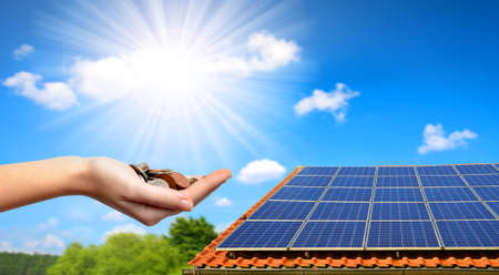 Photo for Solar panel on the roof of the house and coins in hand. The concept of money saving and clean energy. - Royalty Free Image