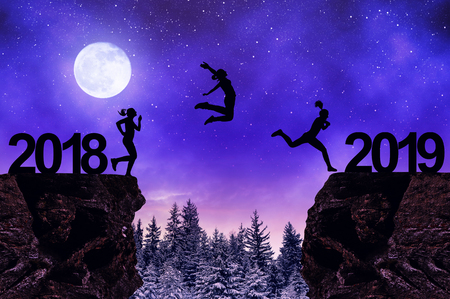 Photo pour Silhouette the girls jump to the New Year 2019 in night. - image libre de droit