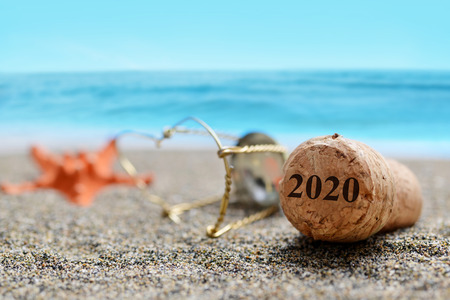 Foto de Cork stopper of champagne with number 2020 and starfish on sand beach. Happy New Year concept. - Imagen libre de derechos