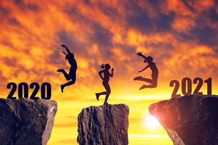 Photo pour Silhouette the girls jump to the New Year 2021 at sunset. - image libre de droit