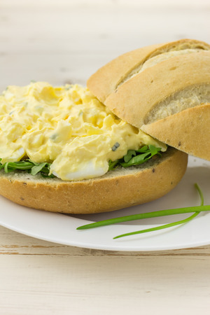 White sandwich with egg and chive salad on a white plate