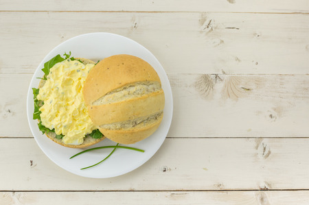 Light bread with egg and chive salad on a white plate