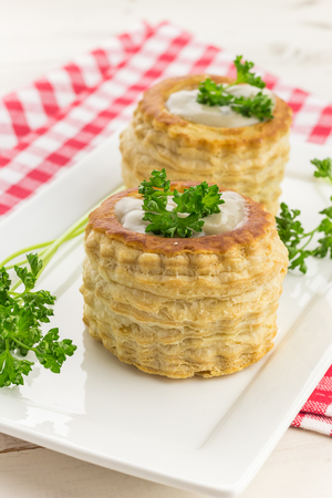 Puff pastry vol-au-vents filled with mushroom ragout, topped with fresh parsley