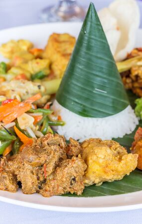 Photo pour Nasi Campur Bali with tempeh, chicken and vegetables, served on a banana leaf - image libre de droit