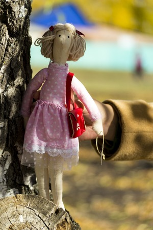 A female   doll in colorful clothes is standing near a birch tree trunk. Registration of holidays. Interior fairy doll handmade. Art and creativity. Blurred background, there is a place for text.