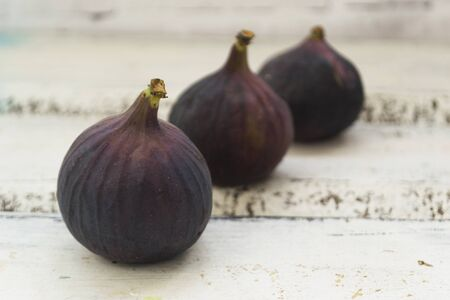 Photo pour Three fresh figs on a wooden white table. Arranged in a row. The concept of urge. - image libre de droit