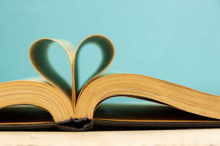 Photo pour The pages of the book are curved in the shape of a heart. Opened book on a blue background. Back to school theme concept. Bibliophile. - image libre de droit