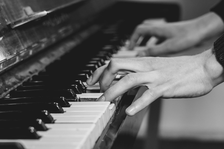 men's fingers on an old piano play