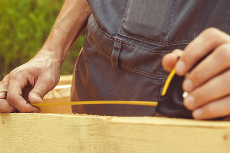 The worker makes measurements of a board with the help of a ruler, a tape measure and a pencil