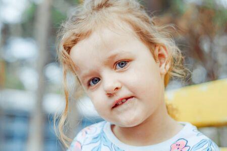 Photo pour little girl joyful on the street sitting on a bench - image libre de droit