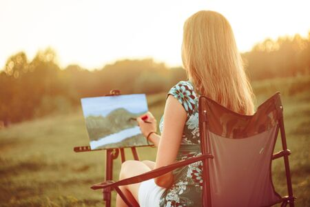 Photo pour girl draws a picture in nature oil painting by the river - image libre de droit