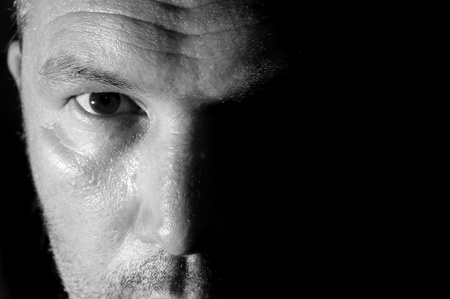 Dark and moody portrait of serious looking male adult
