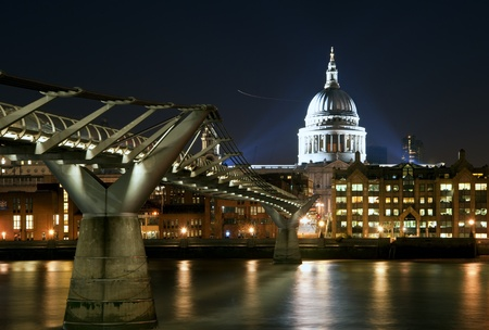 St Paul's Cathedral and Millennium Bridge in London at night with reflections in River Thames with vibrant colors and floodlights