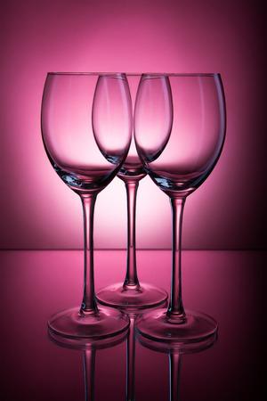 three empty glasses standing frontally on a dark burgundy background