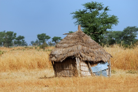 Cob cottage with thatched straw roof in African desert village, Africa.