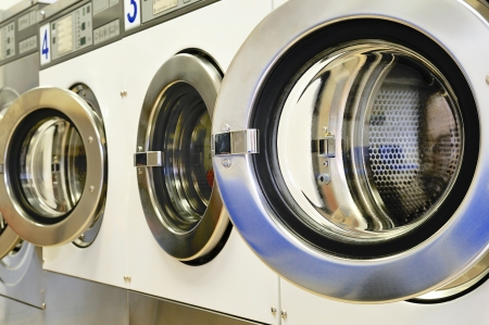 A row of industrial washing machines in a public laundry